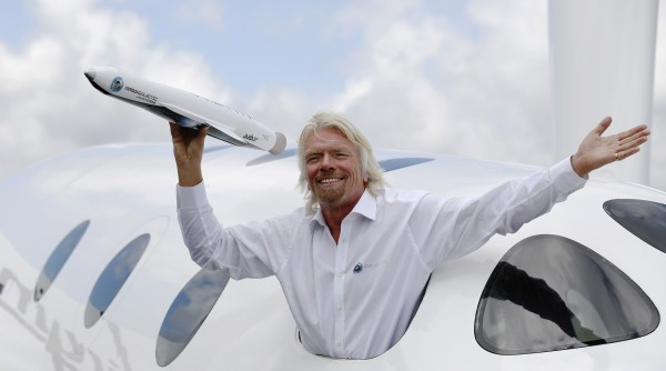Entrepreneur Branson waves a model of LauncherOne cargo spacecraft from a window of an actual size model of SpaceShipTwo on display, after Virgin Galactic's LauncherOne announcement and news conference, at the Farnborough Airshow 2012 in southern England
